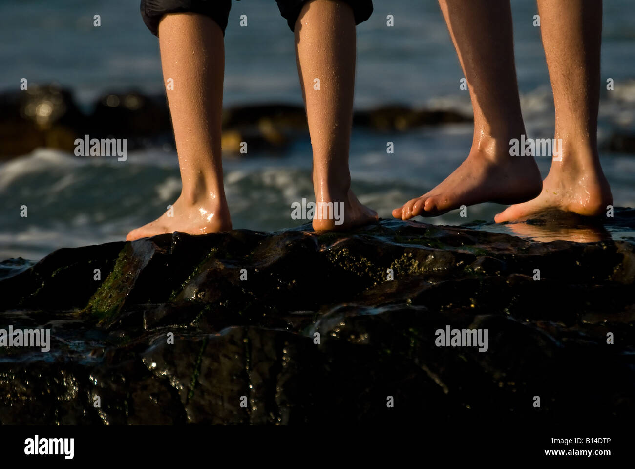 People standing on wet rocks at Sennen in Cornwall. - Stock Image