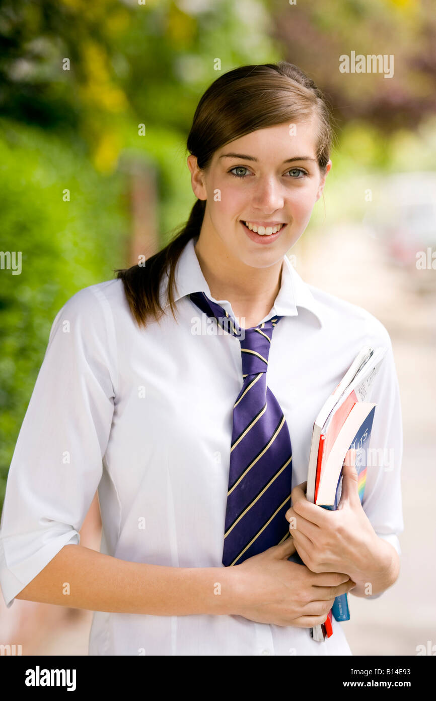 Portrait of pretty smiling teenager wearing school uniform - Stock Image