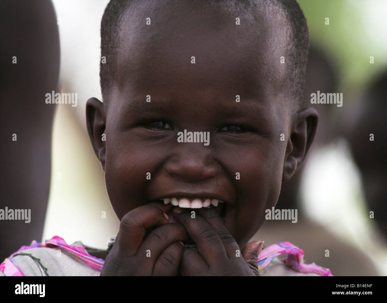 A Dinka girl in Rumbek, South Sudan joyfully looks the camera in the eye - this is her very first photo. - Stock Image
