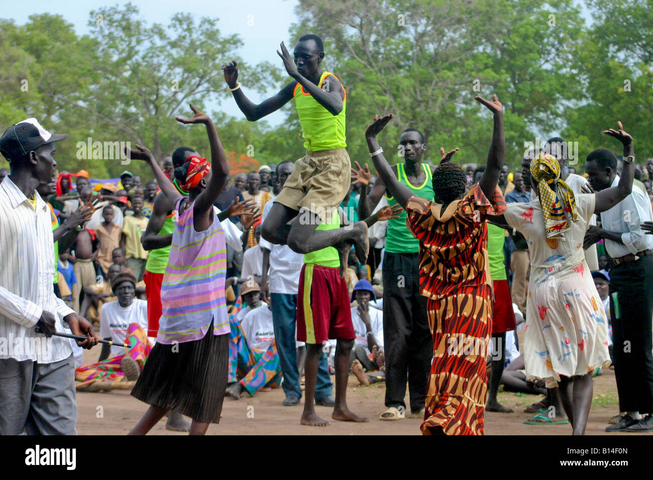 In this photo of traditional Dinka dancing in Rumbek, South Sudan, the women dance, as the men take turns jumping - Stock Image