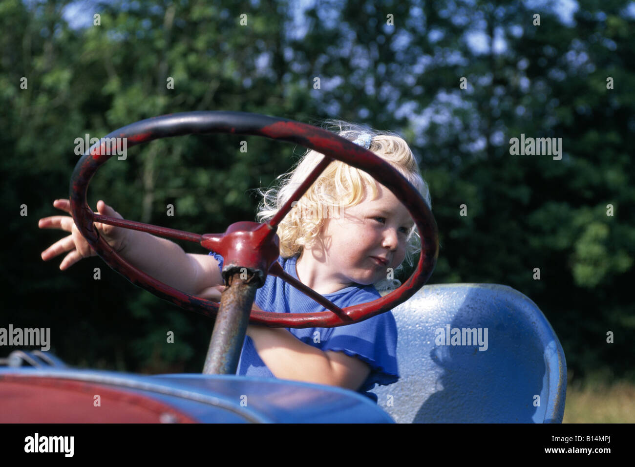 Girl playing on a tractor, open air museum, Angeln, Unewatt, Schleswig Holstein, Germany - Stock Image