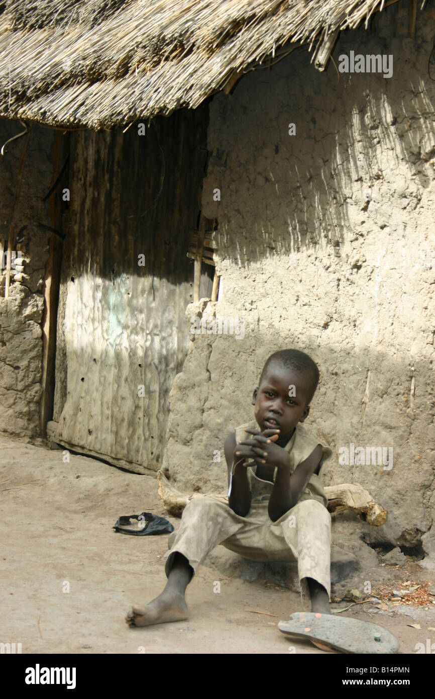 Boy sitting in front of a hut ('tukul') in the Rumbek market, South Sudan. - Stock Image