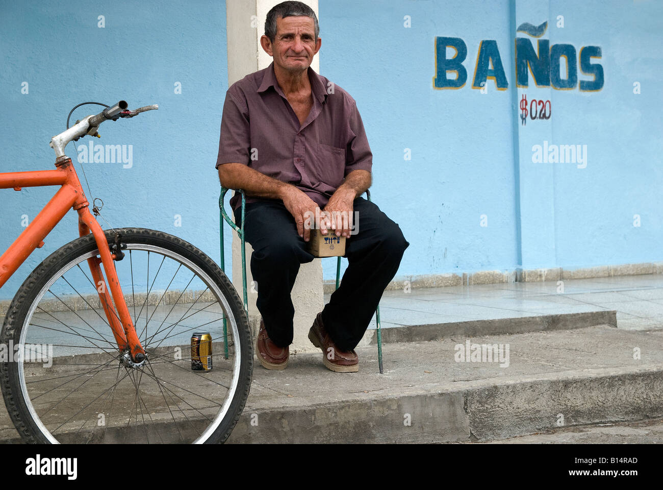 Man sits at the foront of the public toilette, Cienfuegos - Stock Image
