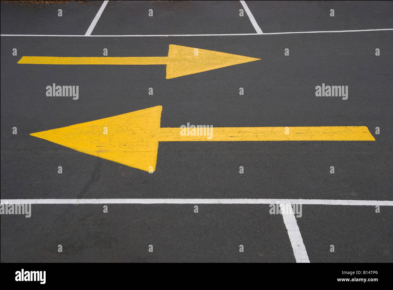 Yellow directional markings pointing in opposite directions - Stock Image