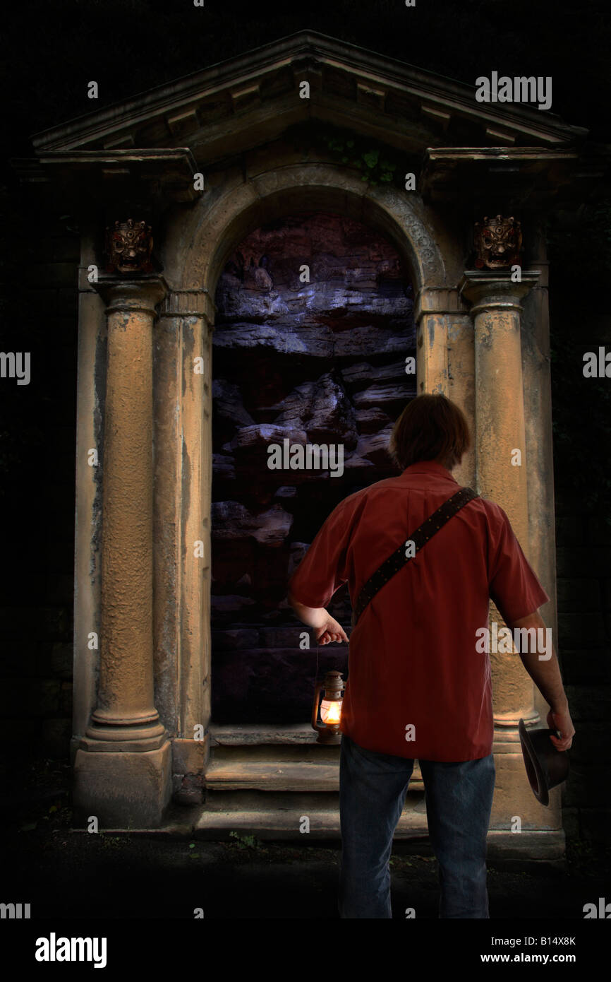 A man discovers an ornate doorway in an underground cave. Stock Photo