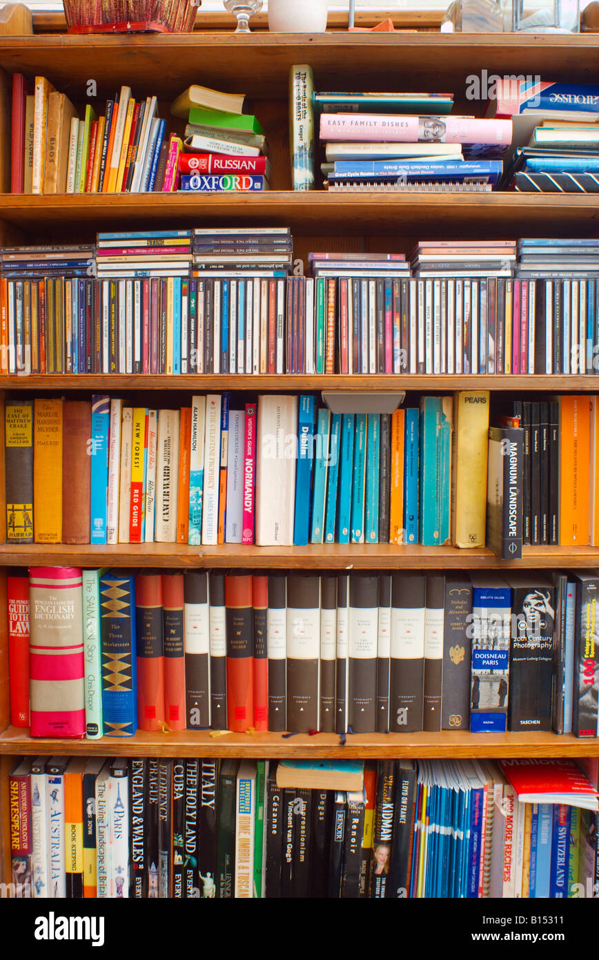 Bookshelf with paperbacks hardbacks CDs - Stock Image