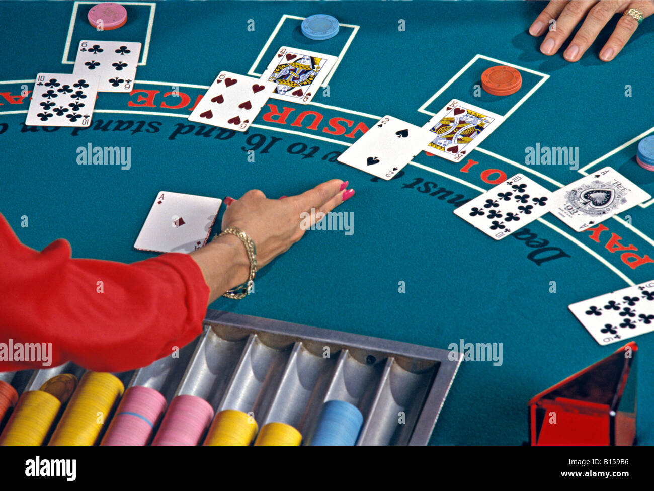 A female blackjack dealer points to cards during a game of 21 in a casino. - Stock Image