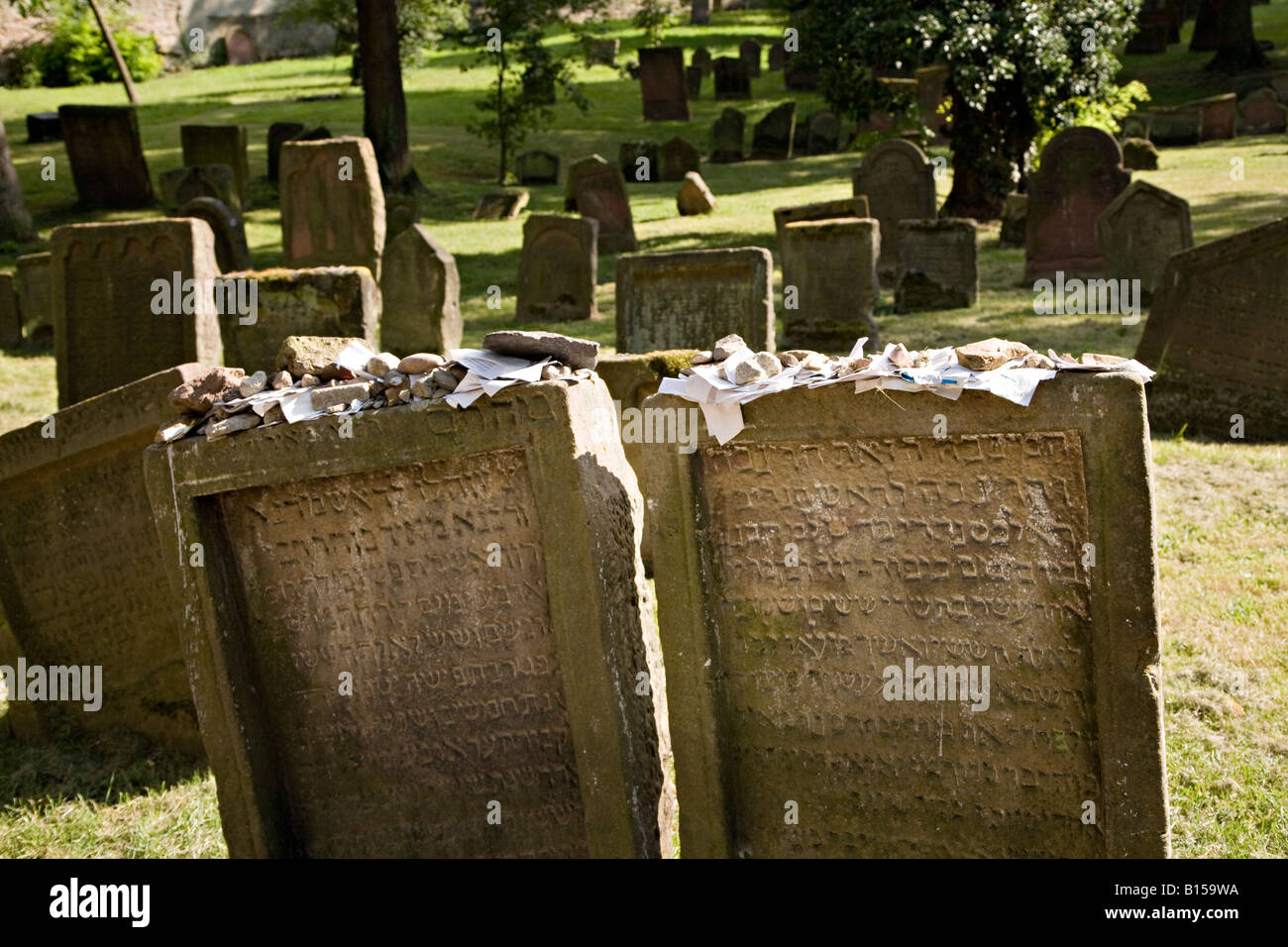 Stones and messages on top of rabbi's gravestone with hebrew writing in Jewish cemetery Worms Germany - Stock Image