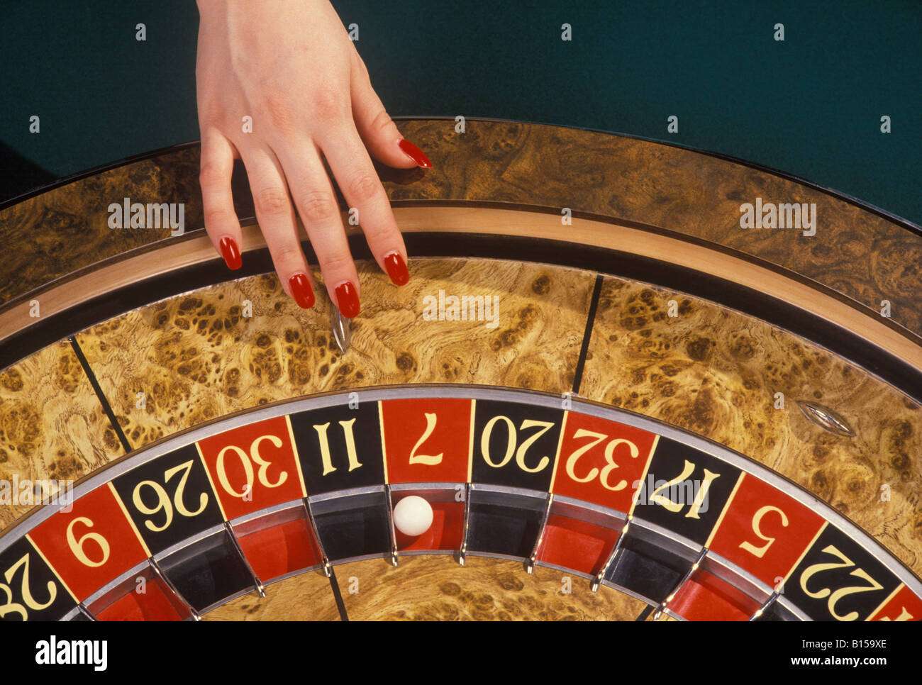A female gambler takes a chance at the roulette wheel in a casino. - Stock Image