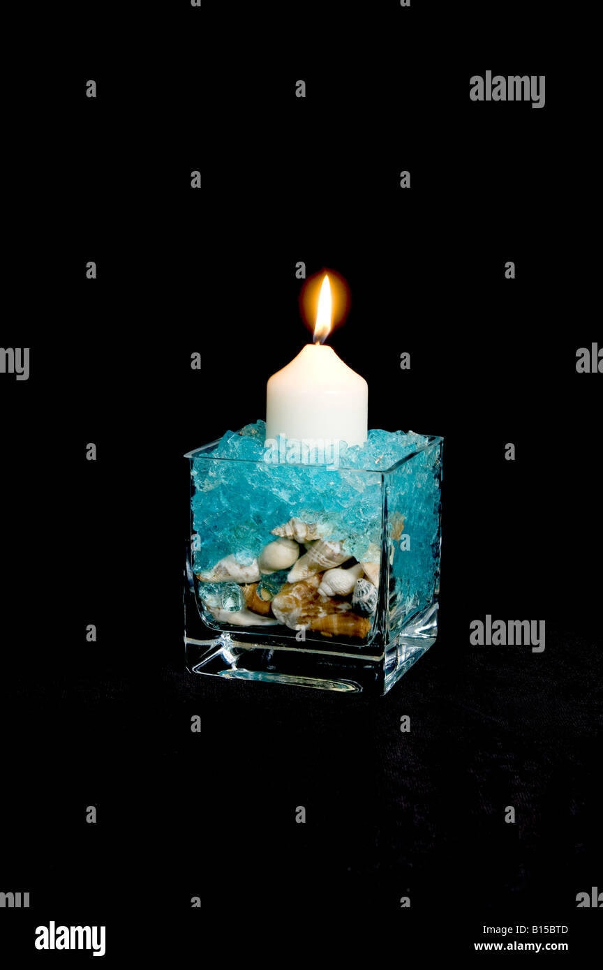Glass cube display of shells and blue gel crystals with candle Stock Photo