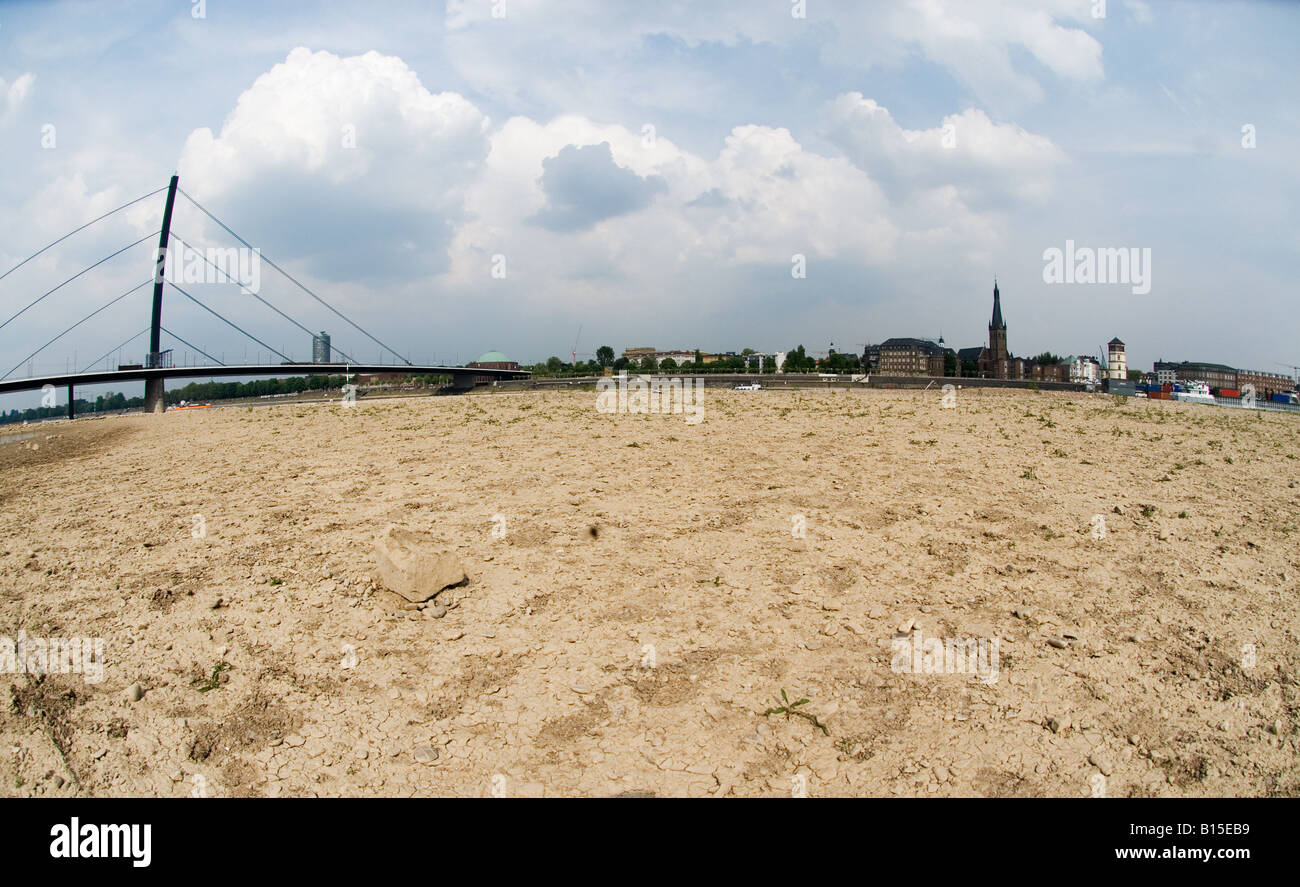 Dried up river banks of the Rhine river in Duesseldorf, Germany across historic Old Town, with Oberkasseler Bridge - Stock Image
