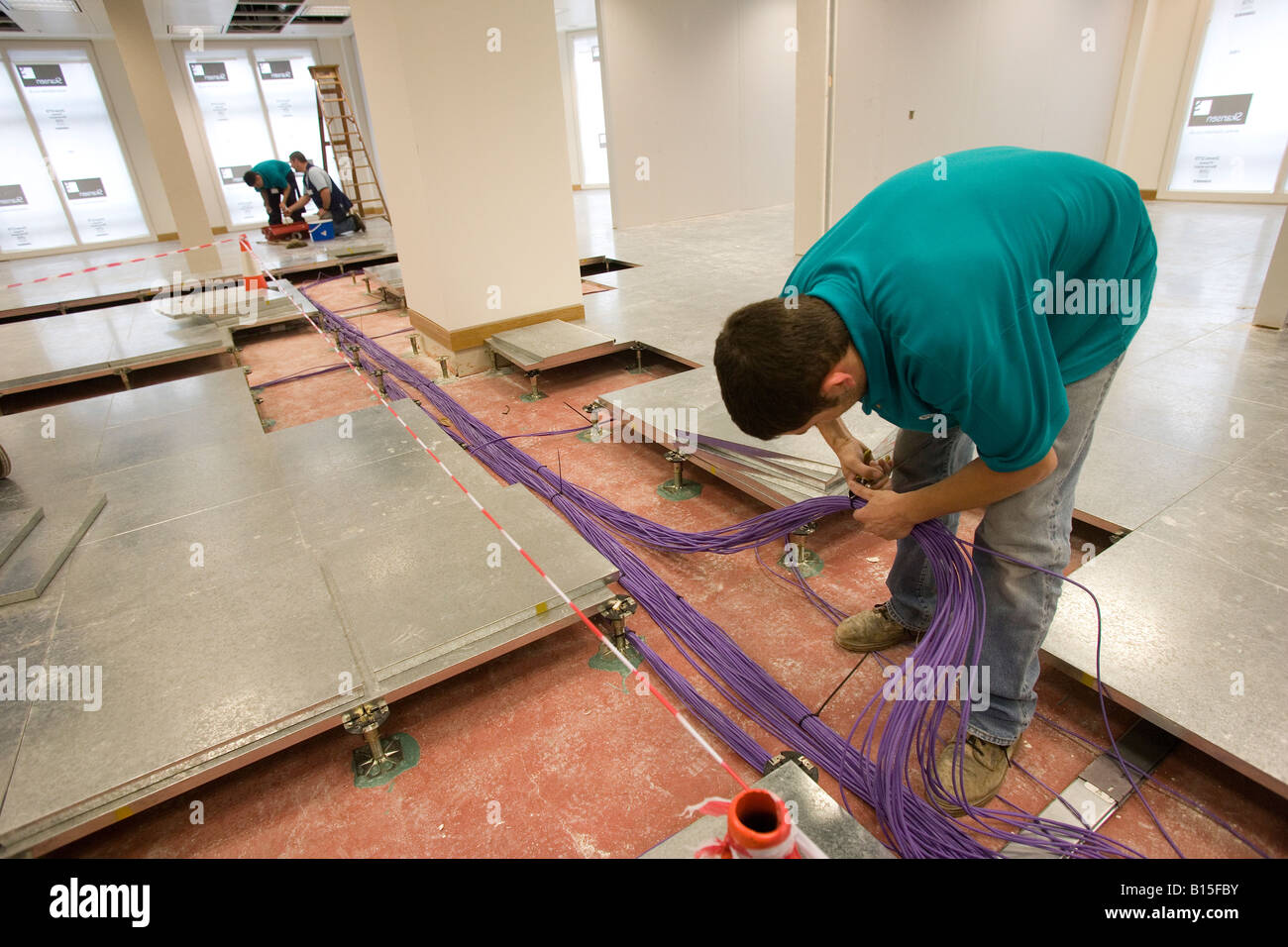 Data cabling is routed under a raised floor in a newly constructed office building. - Stock Image