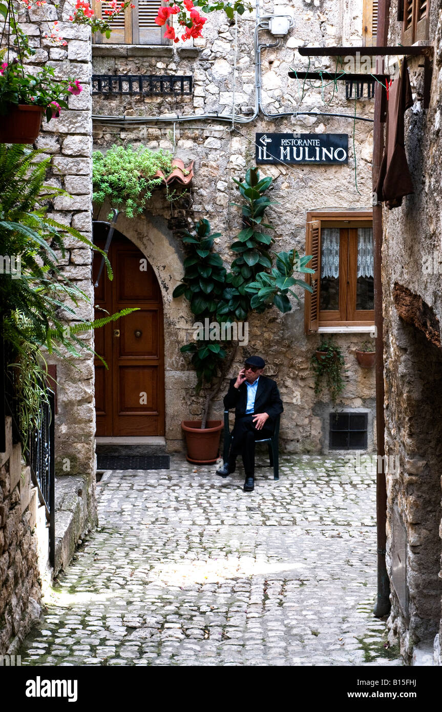 Old man sitting in front of his house in Sermoneta, Italy Stock Photo