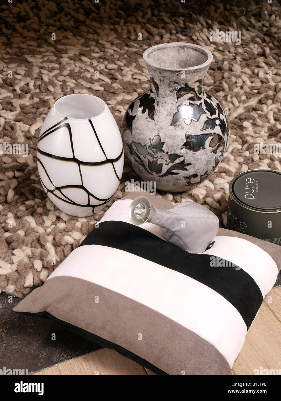 Combining trendy modern interior items in brown grey earth colours vases carpet light pillow - Stock Image
