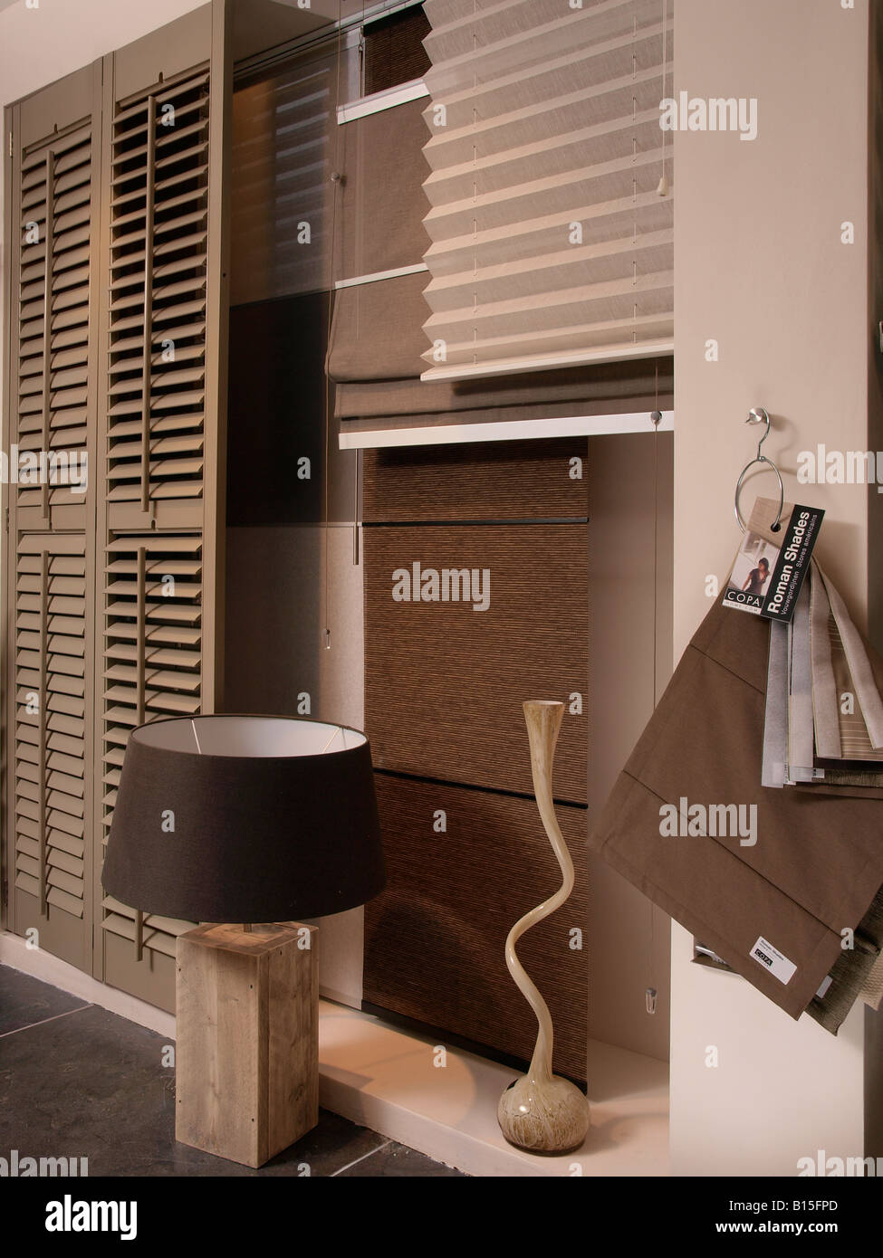 Combining trendy modern interior items in brown grey earth colours shutters lamps vase curtains - Stock Image