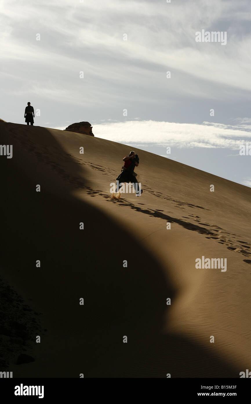 Tourist playing in dune Oued Tin Tarabine Tassili Ahaggar Sahara desert Algeria - Stock Image