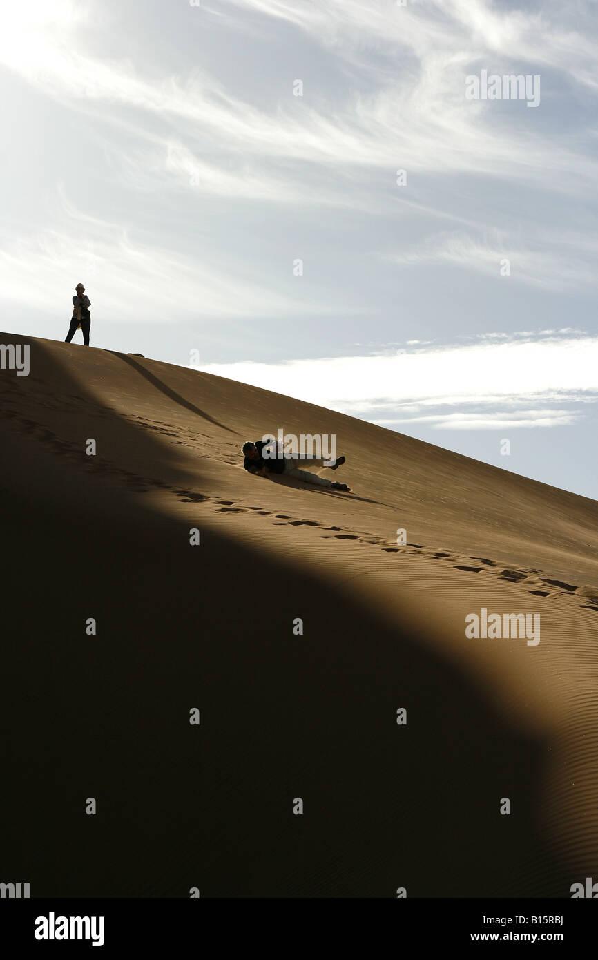 Person playing in dune Oued Tin Tarabine Tassili Ahaggar Sahara desert Algeria Stock Photo
