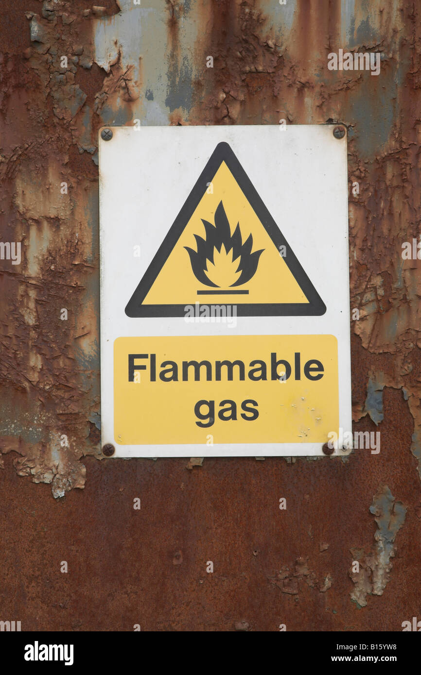 Yellow warning sign for flammable gas on rusty barn door - Stock Image