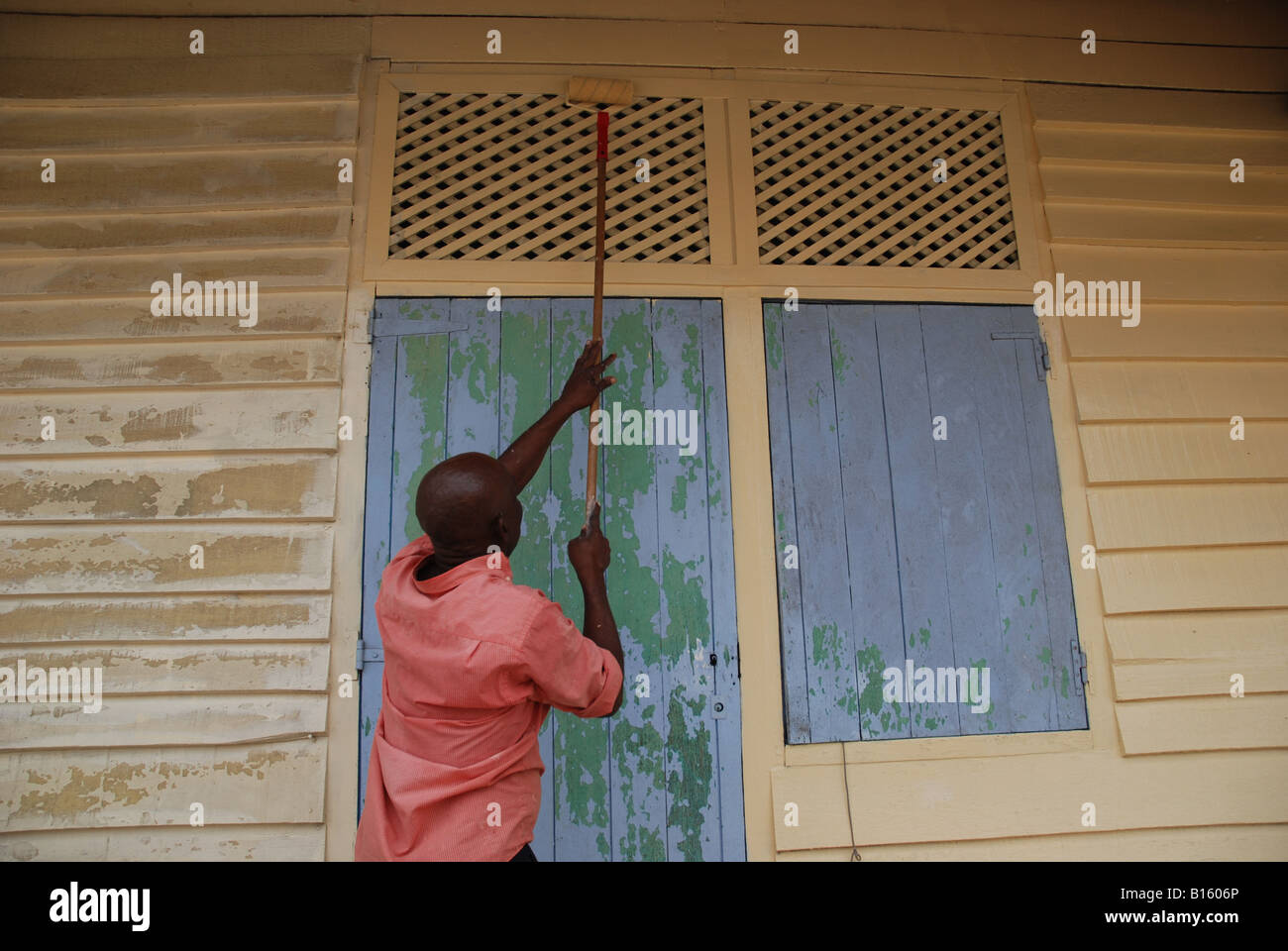 black man painting a front wooden house in french guyana