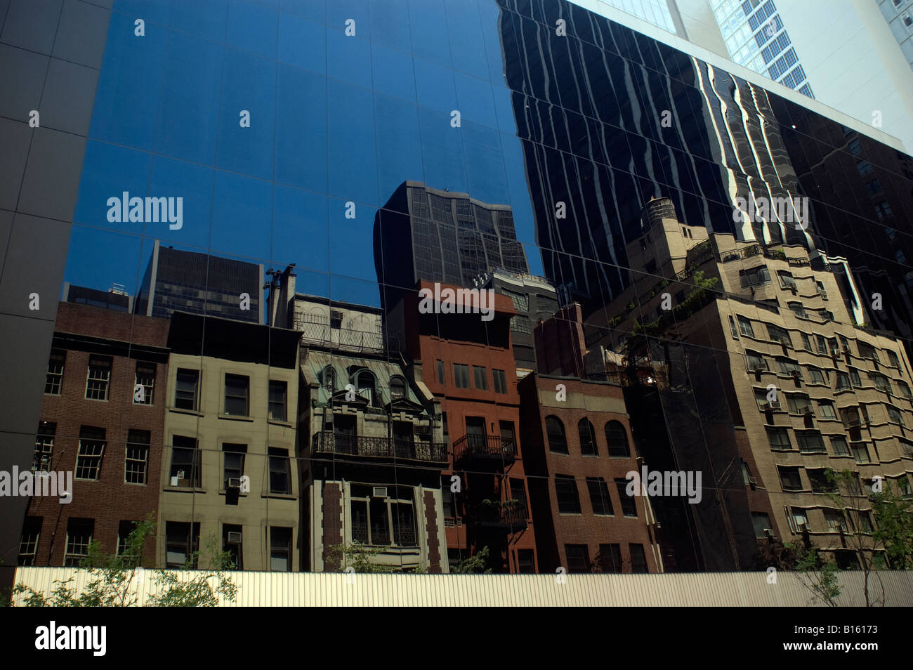 Midtown Manhattan buildings are reflected off the glass walls of the Museum of Modern Art - Stock Image