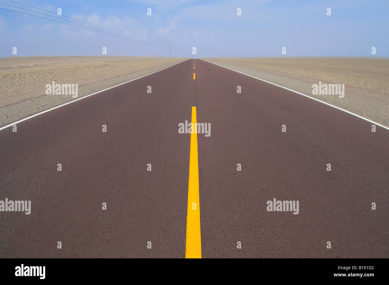 Part of the Pan American Highway in the desert centered and leading off to the distance with yellow dividing lines - Stock Image