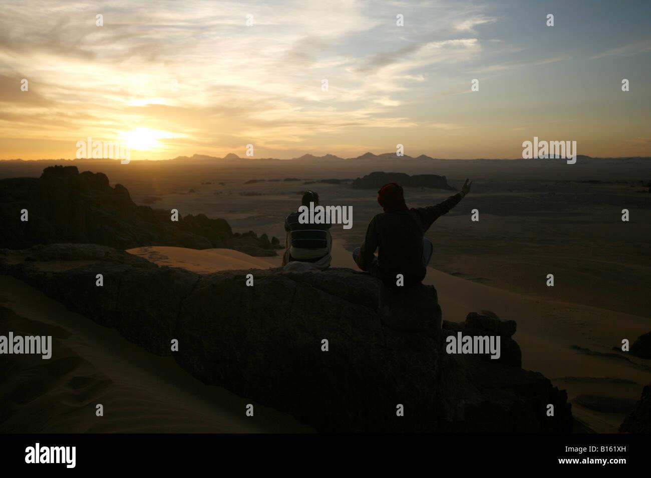 Couple looking at sunset Tagelment Samedat Tassili Ahaggar Sahara desert Algeria - Stock Image