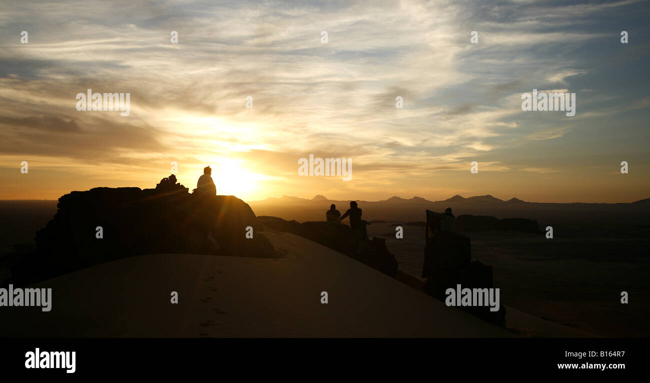 Couple looking at sunset at Tagelment Samedat Tassili Ahaggar Sahara desert Algeria - Stock Image