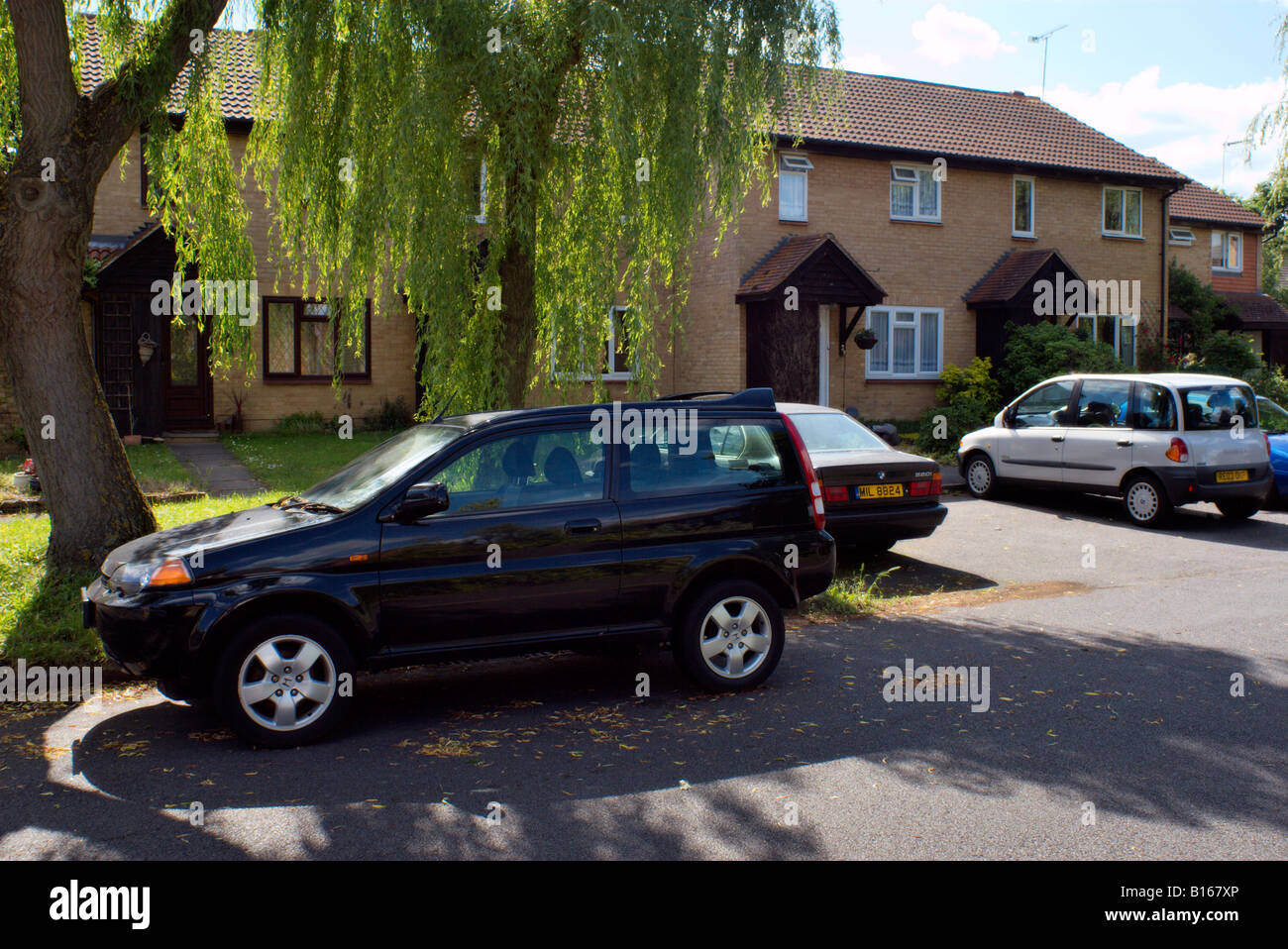 Ordinary suburban scene in Goldsworth Park Woking Surrey England with parked cars and willow tree - Stock Image