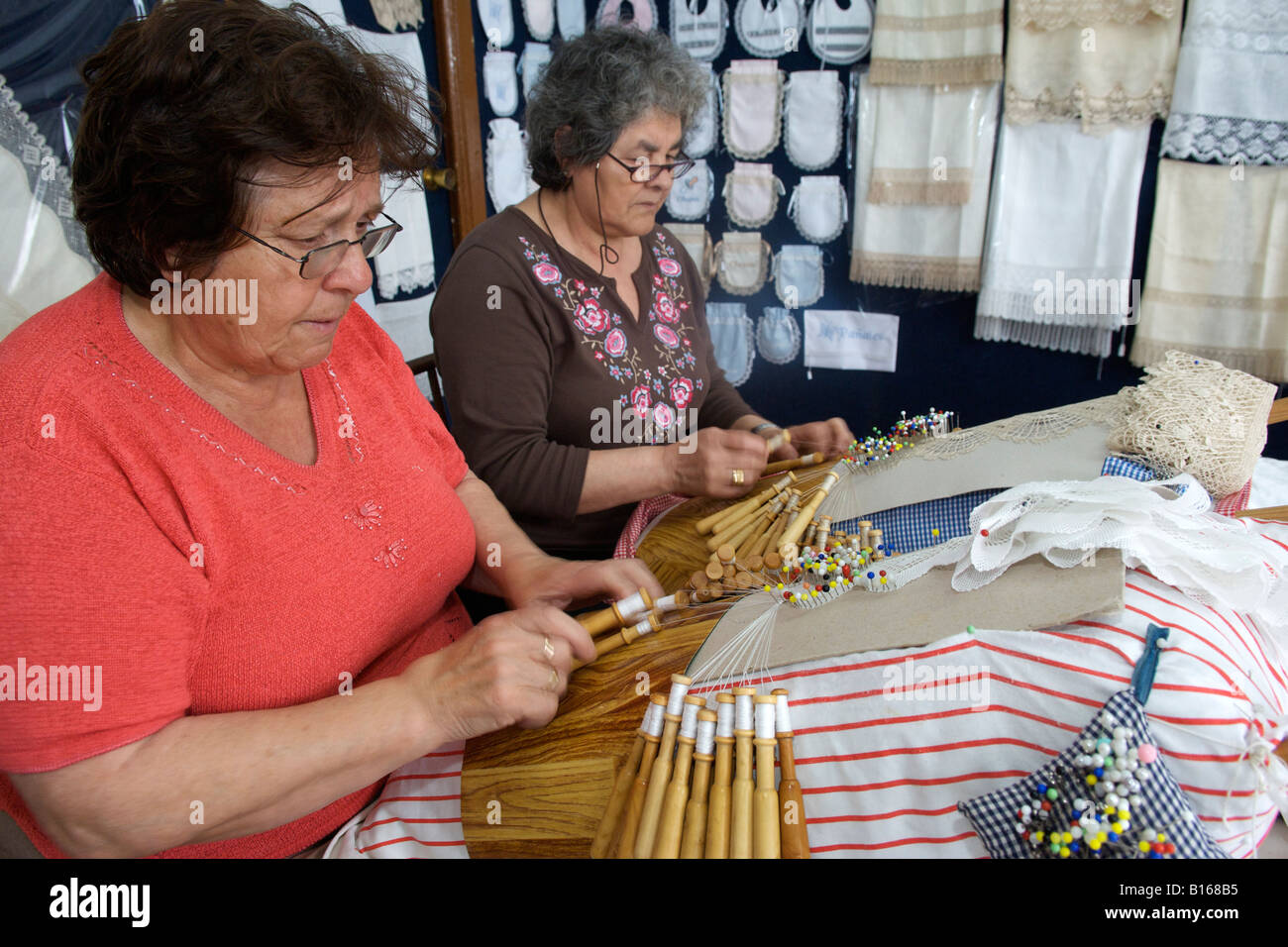 Spanish women weaving lace on their gingham pin cushions in the village of Camariñas in the Galicia region - Stock Image