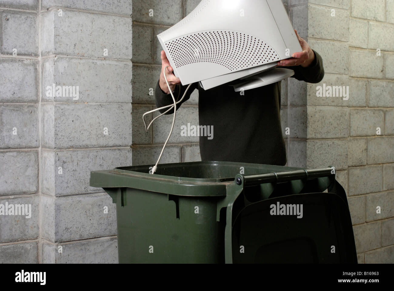 Disposing of obsolete computer technology in a wheelie bin - Stock Image