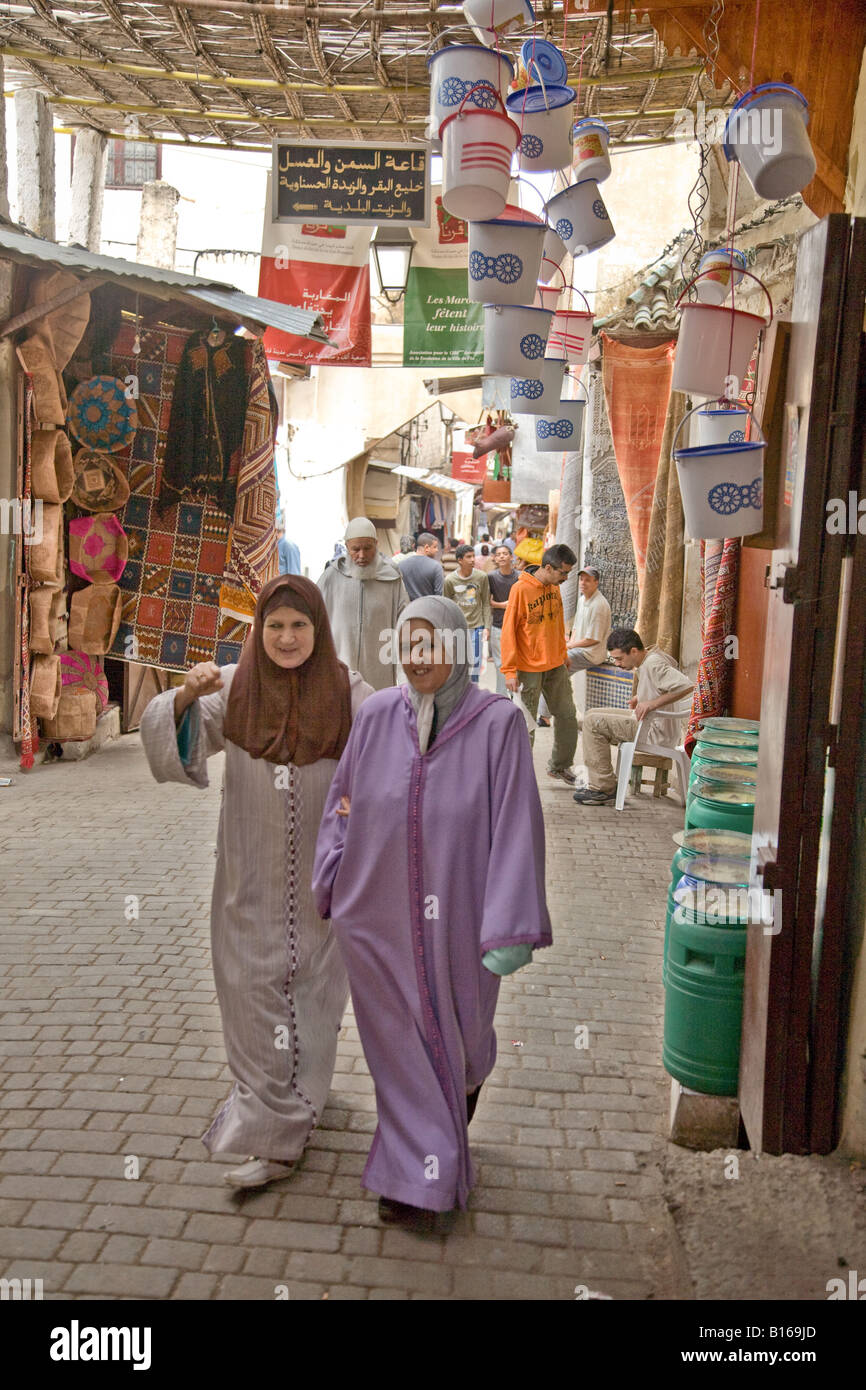Two local women strolling through Souk in Fez  Morrocco - Stock Image