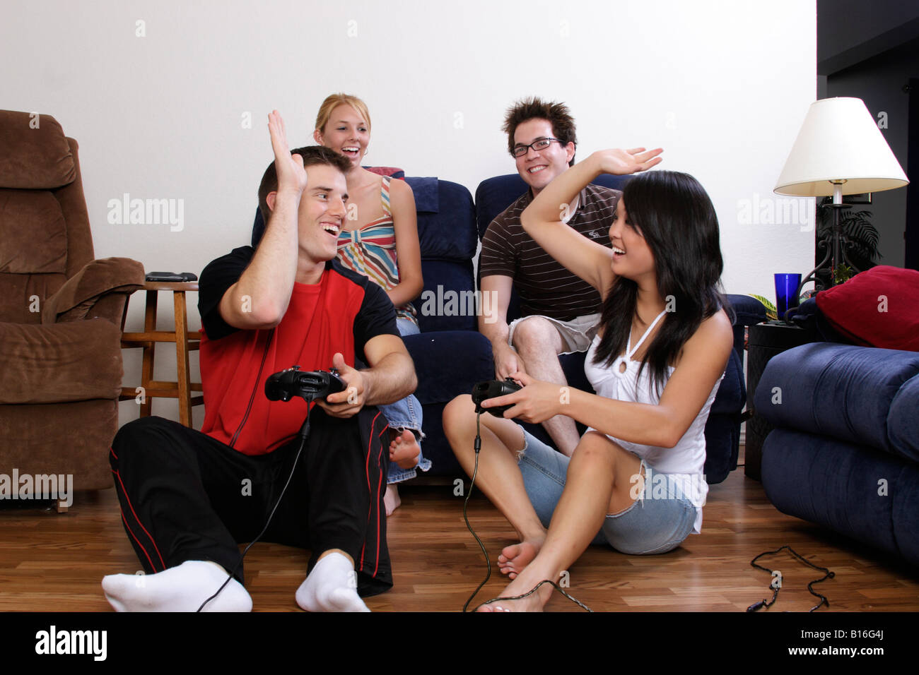 Stock Photograph of four teens having fun playing video games - Stock Image