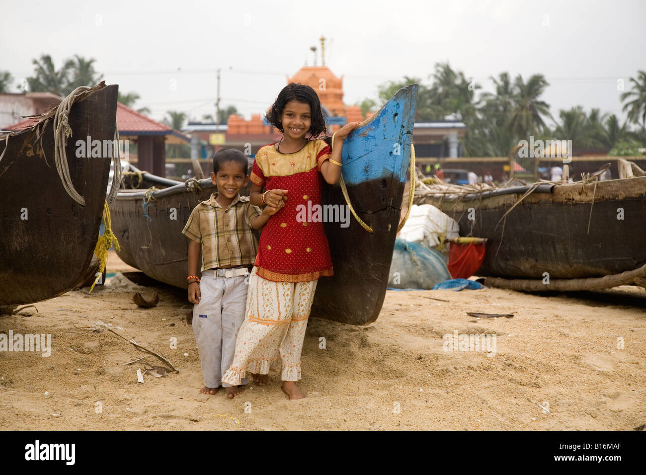 Two children grin for the camera on Kappil Beach in Kasaragod, Kerala. Fishing boats are pulled up on the beach behind them. Stock Photo