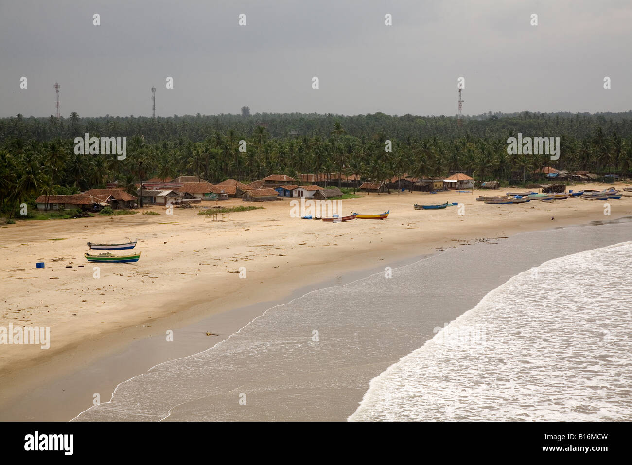 The view onto Bekal Fort Beah from Bekal Fort near Kasaragod, Kerala. Fishing boats stand on the golden sand. - Stock Image