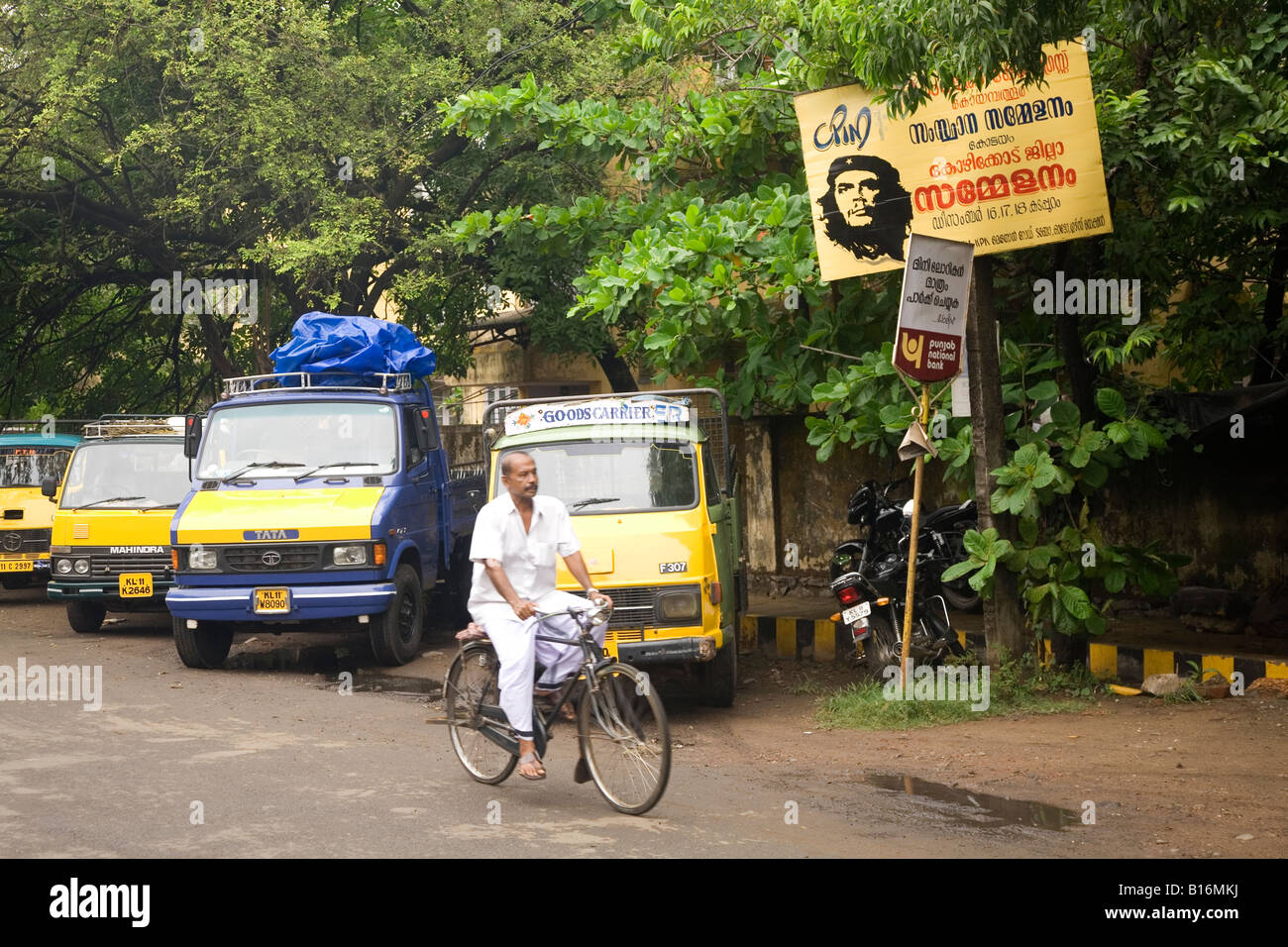 Trucks park near to the Big Bazar Road in Kozhikode. A man in a dhoti cycles past the parked vehicles. - Stock Image