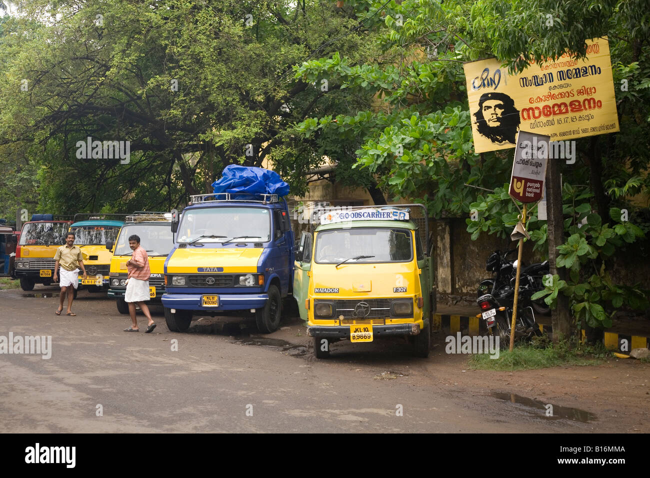 Trucks park near to the Big Bazar Road in Kozhikode. Men in dhotis walk past the parked vehicles. - Stock Image