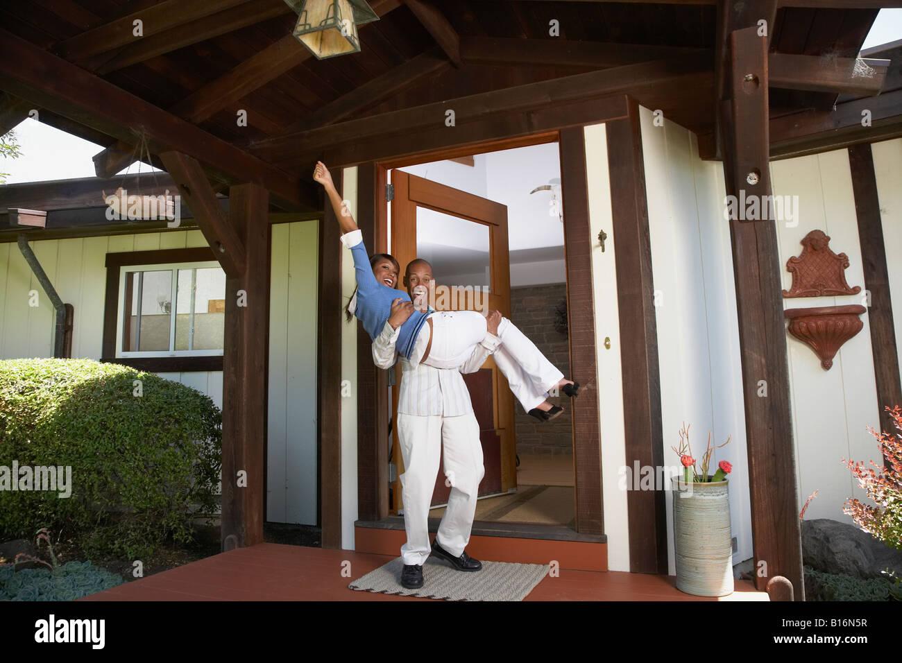 African man carrying wife in doorway Stock Photo