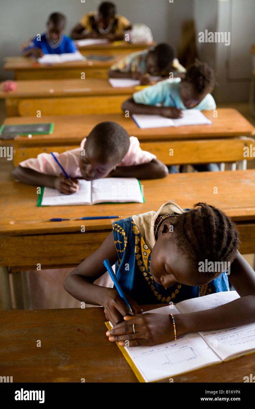 Children write exams in classroom - Stock Image