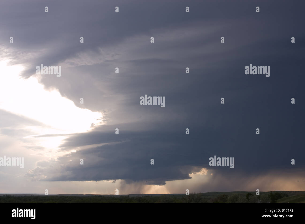 Evening cumulonimbus clouds with developing thunderstorm and rain with small funnel cloud in cumulus clouds in center - Stock Image