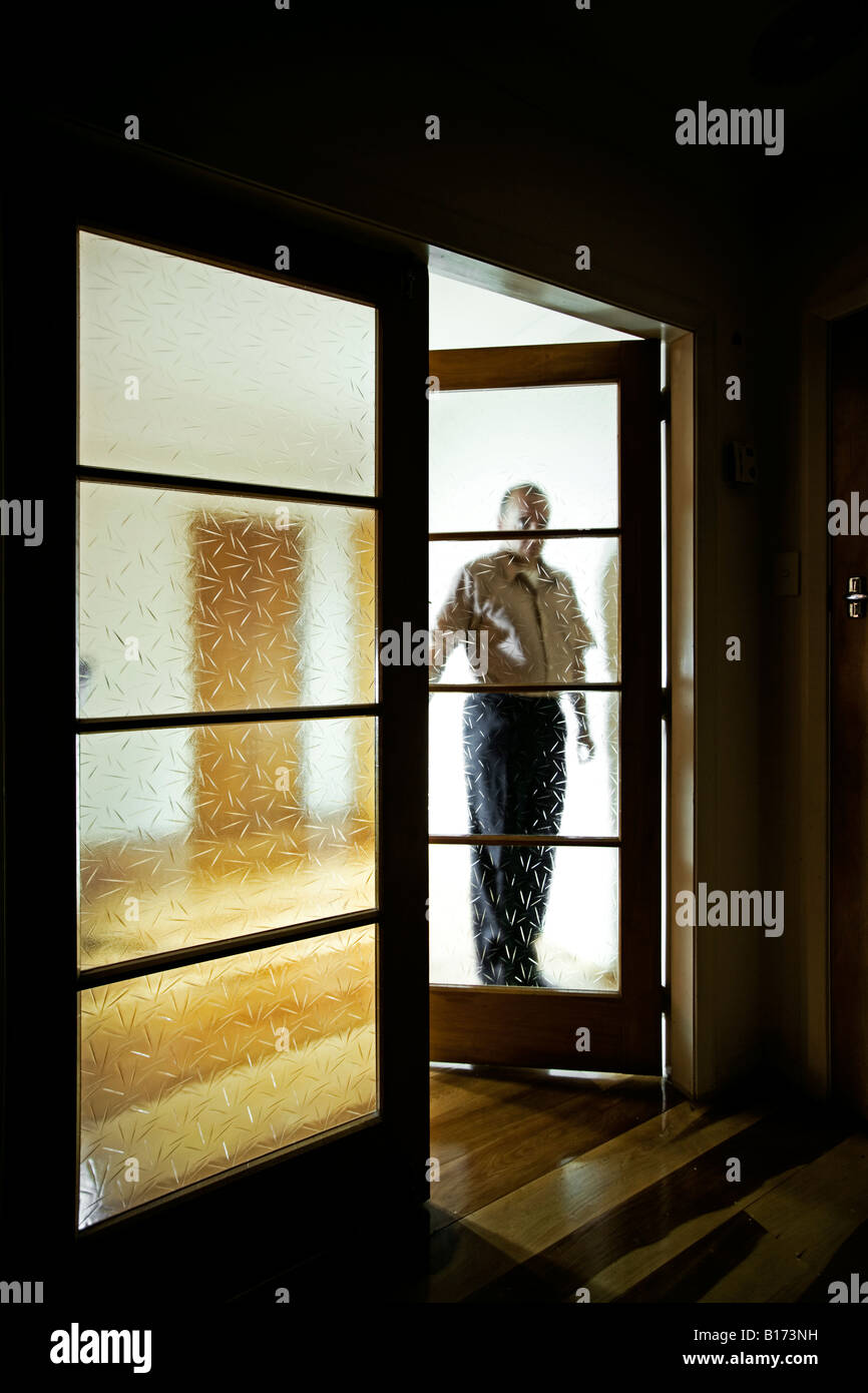 Man by double glass interior doors in a darkened room - Stock Image