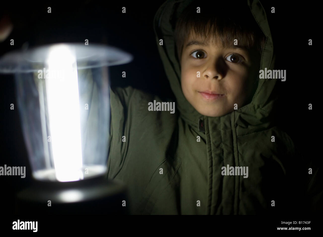 Boy aged six holds up electric lantern wearing a hooded green coat - Stock Image