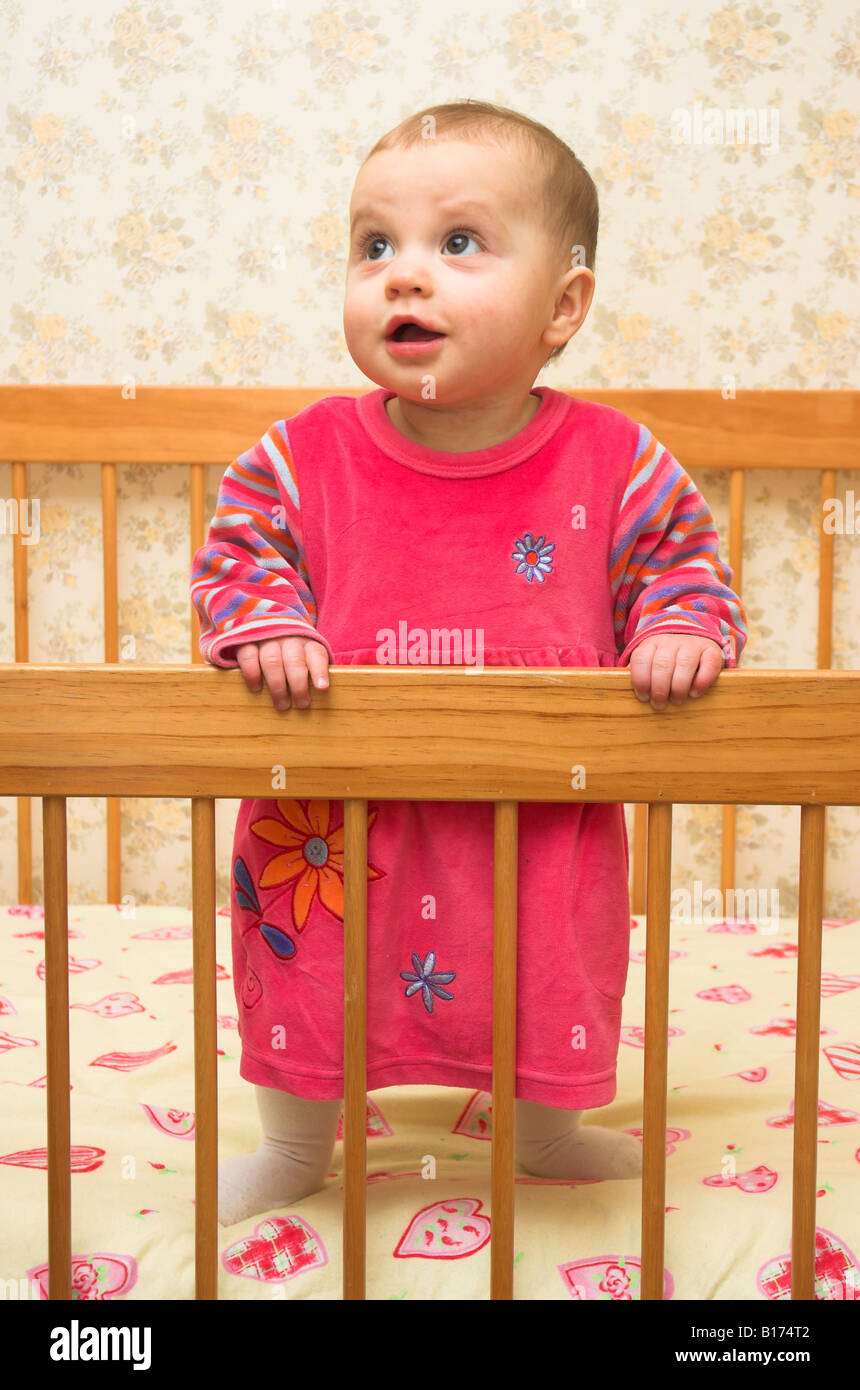 A cute 9 month old baby standing up in her cot - Stock Image