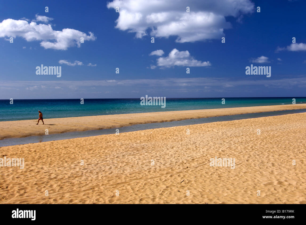 A man walking along the beach of the Portuguese Atlantic island of Porto Santo. - Stock Image