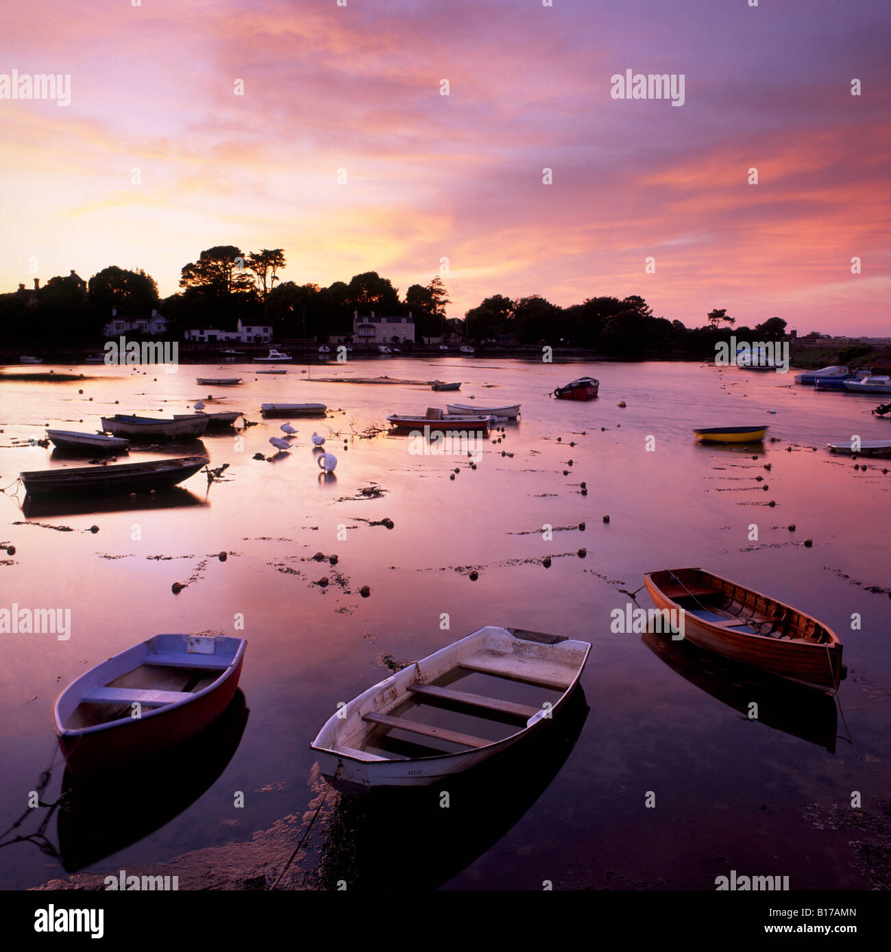 View of a beautiful sunset across Cockwood Harbour, Devon, UK with boats in the foreground - Stock Image