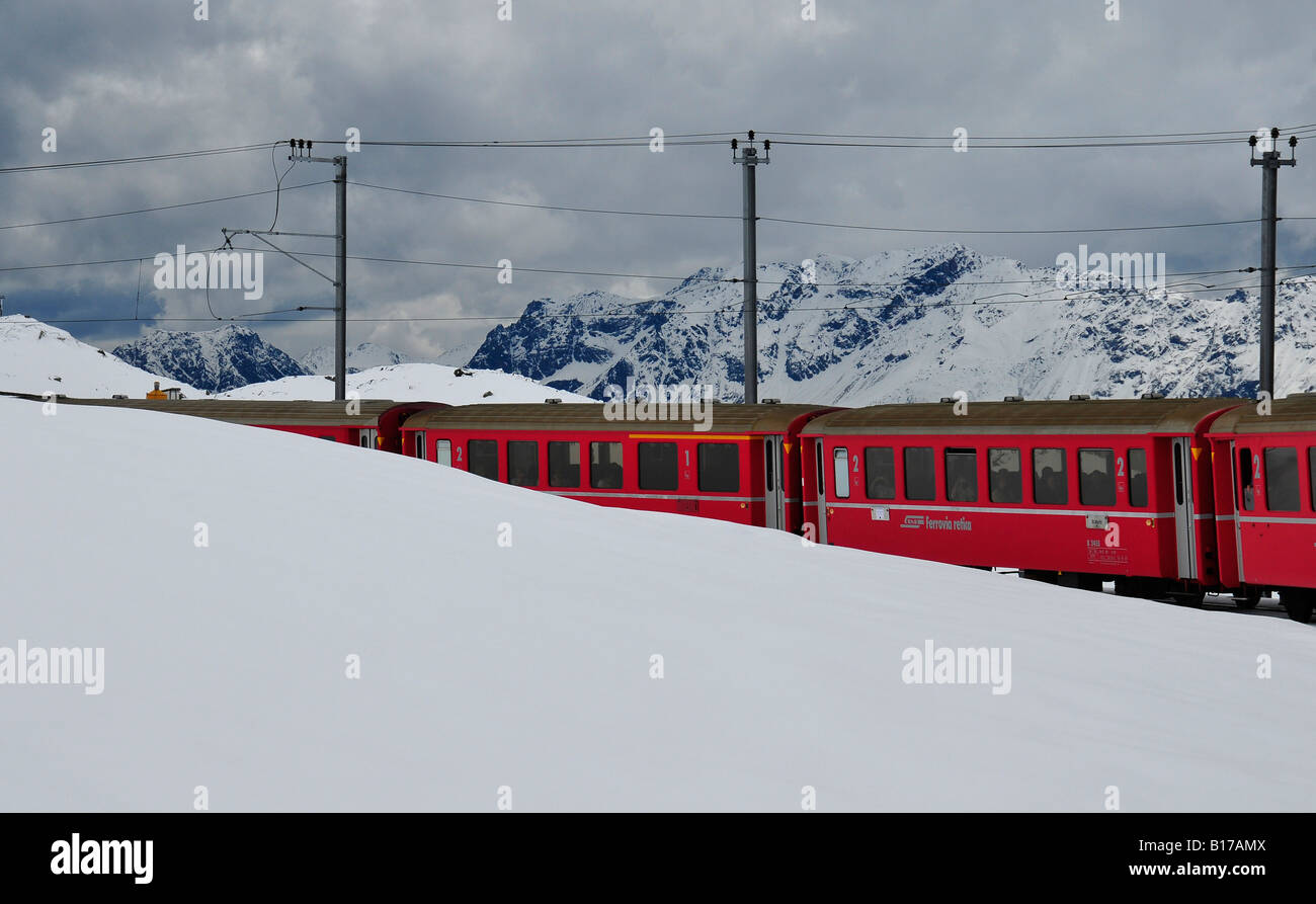 Bright red train carriages appearing from snow covered mountain slopes in the Swiss alps. Full of tourists on a - Stock Image