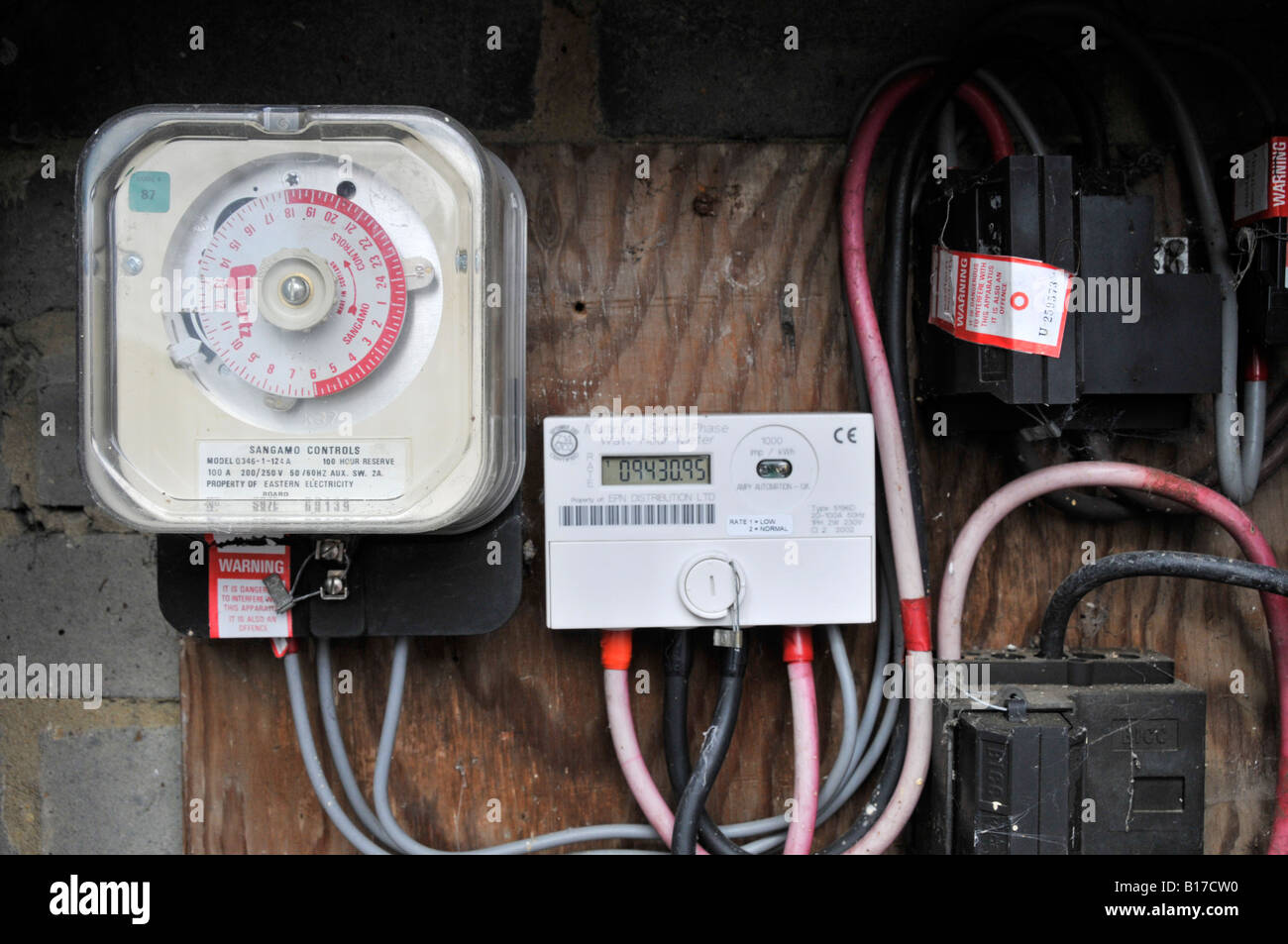 Domestic electricity meter with time clock that switches night time meter readings on and off all housed in external - Stock Image