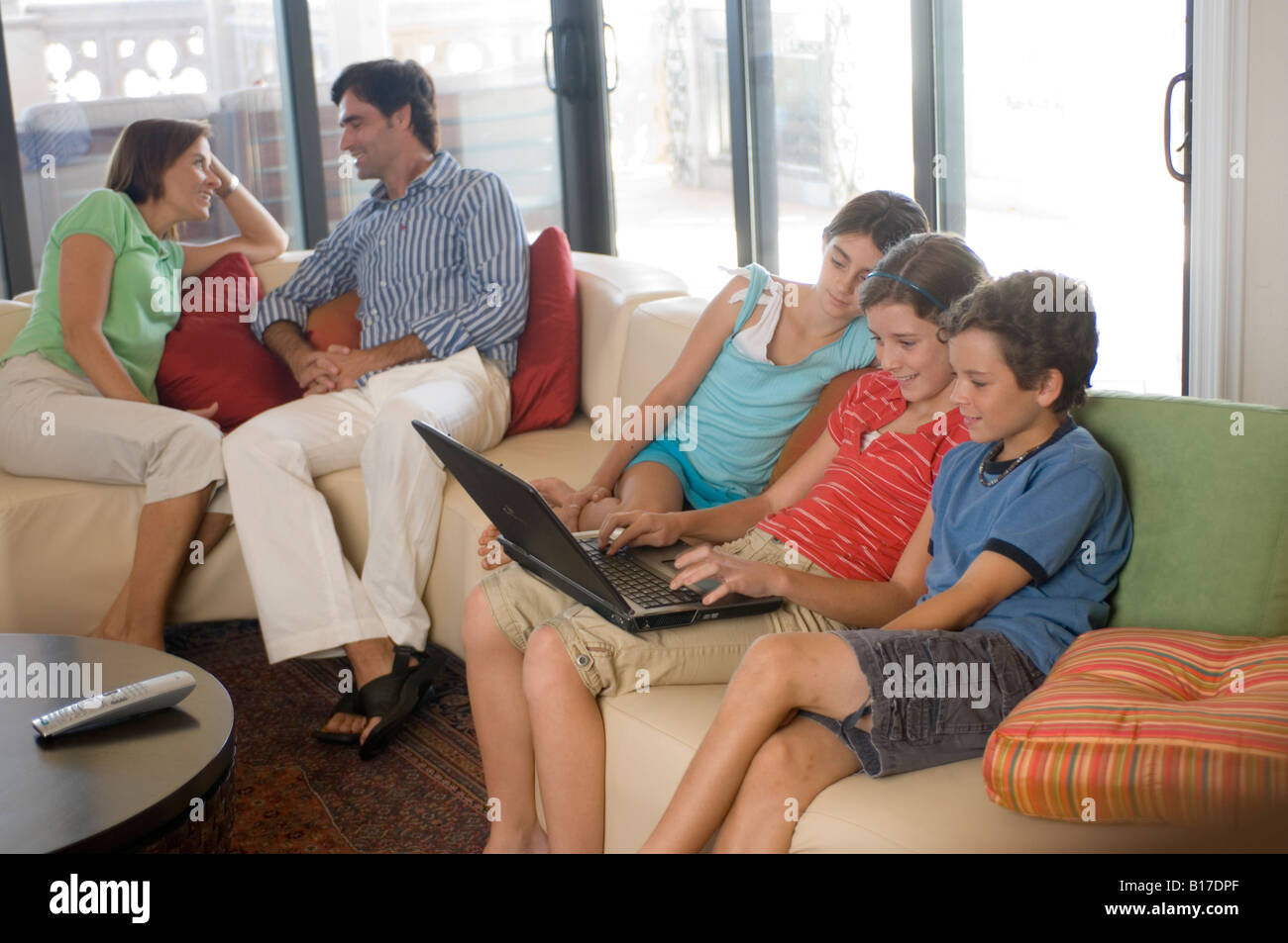 Kids at home on Laptop computer with parents - Stock Image