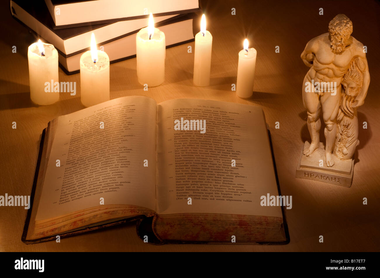 Still-life with an old Latin book of Virgil's Aeneid, candles and antique statue of Heracles. - Stock Image