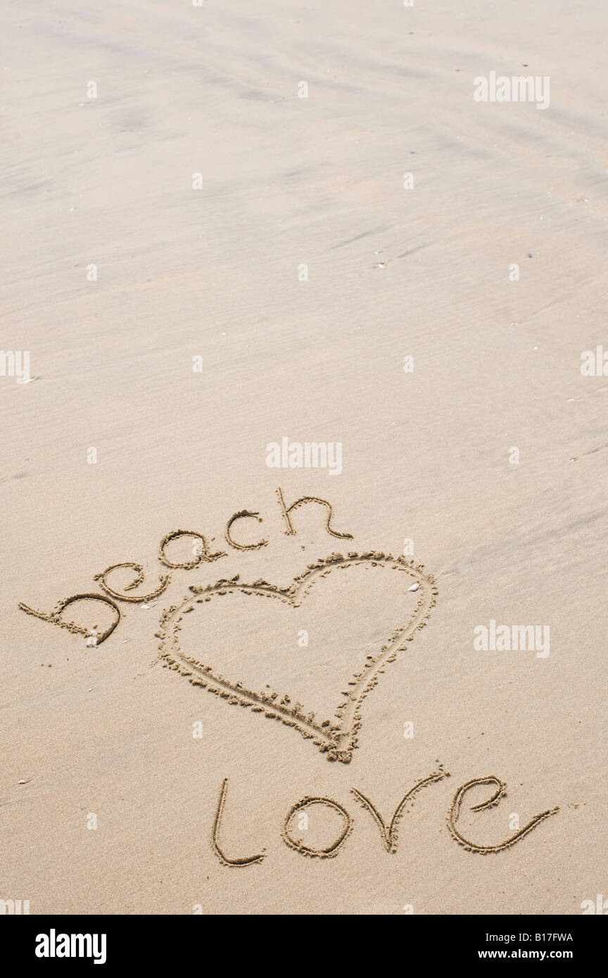 Heart shape and words 'beach love' drawn in the sand on a beach. UK - Stock Image