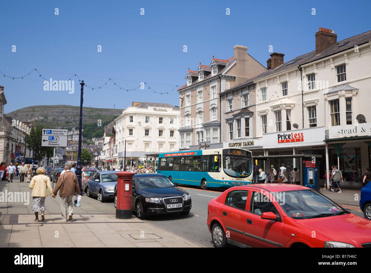 Traffic and pedestrians in busy high street with shops in Victorian buildings in town centre. Llandudno North Wales Stock Photo